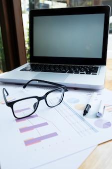 Bureau avec ordinateur portable et lunettes sur table en bois.