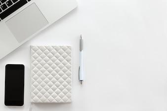 Bureau bureau blanc avec une partie d'ordinateur portable, téléphone mobile, stylo