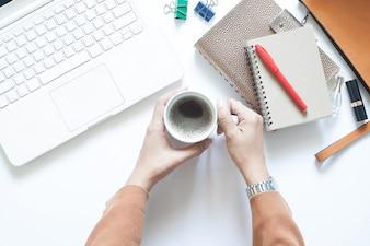 Bureau de bureau blanc moderne avec une femme d'affaires tenant une tasse de café, Flat Lay