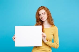 Business Concept - Close up Portrait jeune belle attrayante fille redhair souriante montrant signe vide. Blue Pastel Background.