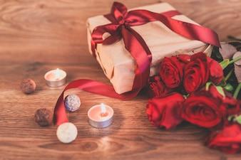 Cadeau avec des bougies et des roses allumées