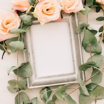 Cadre blanc avec des fleurs et des feuilles