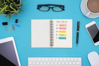 Cadre de but intelligent avec fournitures de bureau sur bureau bleu