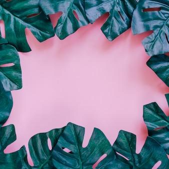 Cadre de feuilles de palmier vert sur fond rose pour un design d'affiche ou de modèle