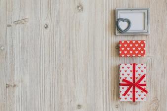 Cadre et polka cadeaux gris sur une table en bois