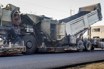 Camion décharge l'asphalte à la machine pour réparer la route