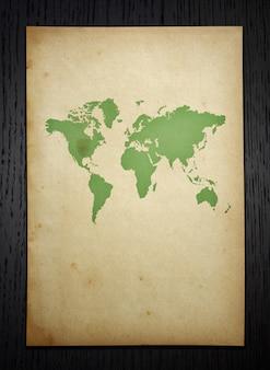 Carte du monde vintage sur fond de bois sombre avec tracé de découpage