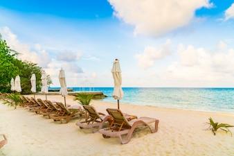 Chaises de plage avec parasol à l'île des Maldives, plage de sable blanc et mer