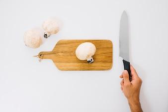 Champignons et main avec un couteau