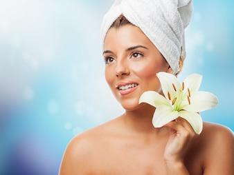 Charmante femme avec une serviette blanche portant lys sur la tête