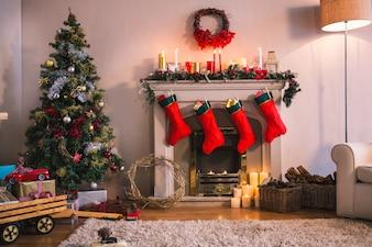 Cheminée avec des chaussettes rouges suspendus et un arbre de Noël