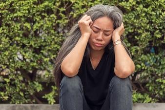 Cheveux gris de femme avec une expression de visage stressée inquiète regardant vers le bas