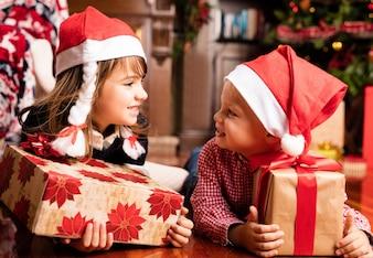 Childrens regardant les uns les autres avec des cadeaux