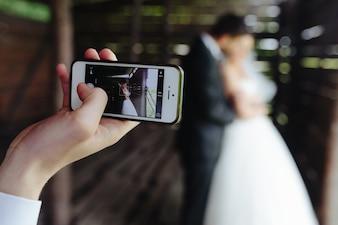 Close-up de la téléphonie mobile de prendre une photo des jeunes mariés