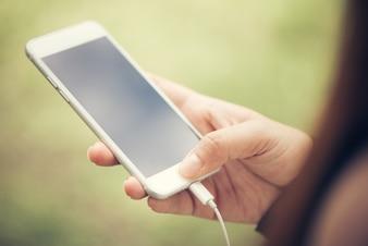 Close-up hand touch sur le téléphone mobile écran blanc vierge concept de style de vie en plein air sur le fond de la nature floue - peut être utilisé maquette image. Photos de style effet effet vintage.