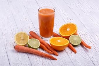 Coccinelle orange avec des oranges et des carottes repose sur la table blanche