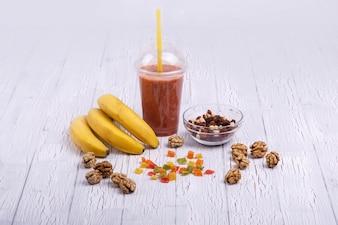 Cocto à detox rouge avec des bananes sur fruits confits se trouve sur la table blanche