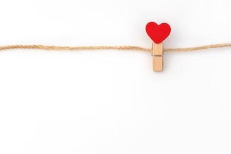 Coeur de papier rouge accroché sur fond blanc.