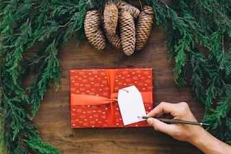 Composition pour Noël avec la main qui écrit sur la boîte de cadeau