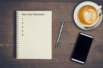 Concept d'affaires - Vue de dessus écriture de cahier Résolution de Nouvel An, stylo, tasse à café et téléphone sur table en bois.
