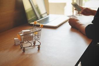 Concept de magasinage en ligne Internet avec ordinateur portable et shopping-cart.Vintage ton effet de filtre rétro, flou artistique (mise au point sélective)