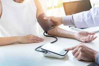 Concept de soins de santé, d'hôpital et de médecine - médecin et patient mesurant la tension artérielle