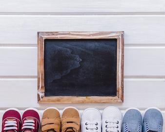 Concept nouveau-né avec ardoise et chaussures