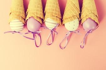 Cones de glace colorés aux oeufs de pâques sur fond rose. Vanille ou Pastel Toning. Minimalisme. Flat Lay.