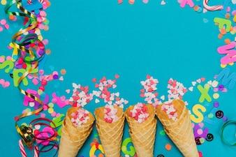 Cornets de crème glacée avec des coeurs et des confettis sur un fond bleu