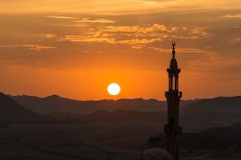 Coucher de soleil avec la mosquée musulmane au premier plan