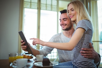 Couple assis à table et en utilisant la tablette numérique dans cafà ©