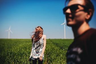 Couple avec des lunettes de soleil sur un champ vert