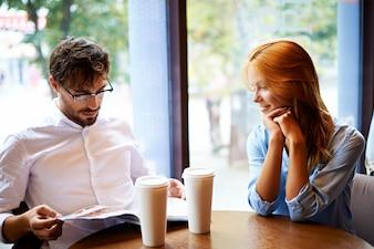 Couple avec le magazine dans un coffee shop