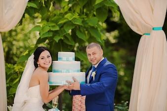 Couple avec un gâteau de mariage dans leurs mains