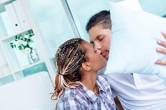 Couple cacher et embrasser derrière un coussin blanc