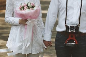 Couple de la main avec un bouquet et un vieil appareil photo