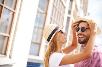 Couple heureux de jouer avec les chapeaux