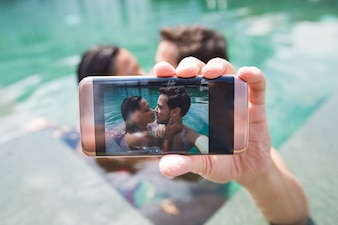 Couple interracial faisant de la photo Selfie dans la piscine