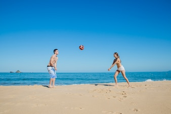 Couple jouant au ballon à la plage