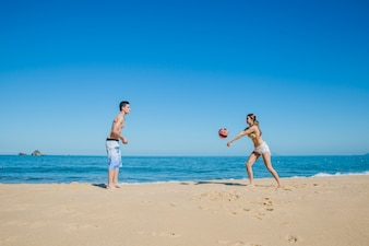 Couple jouant au beach-volley au rivage