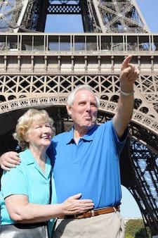 Couple senior pointant quelque chose devant la Tour Eiffel à Paris