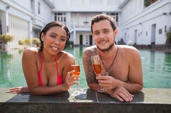 Couple souriant avec du champagne au bord de la piscine
