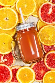 Cruche en verre avec une paille et des oranges coupé autour