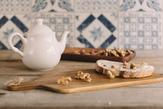 Décoration vintage avec des noix sur planche en bois et pot de thé