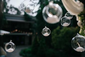 Des boules de verre avec des bougies pendent de l'autel du mariage