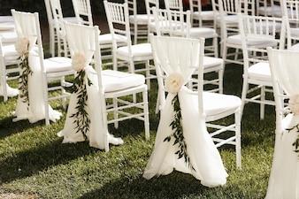 Des chaises blanches décorées de pivoines et de verdure se tiennent à l'extérieur