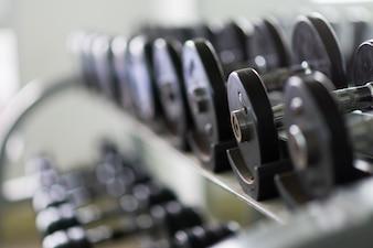Des rangées d'haltères en métal sur le rack dans la salle de sport / club de sport. Équipement de musculation.