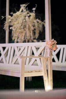 Des roses se tordent autour d'un banc qui se dresse dans l'obscurité