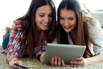 Deux belles jeunes femmes utilisant la tablette numérique à la maison.