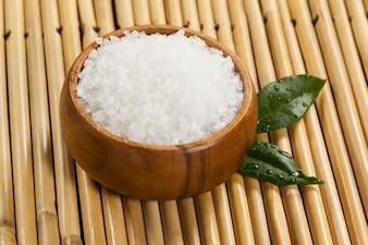 Deux feuilles vertes et le sel de mer dans un bol en bois
